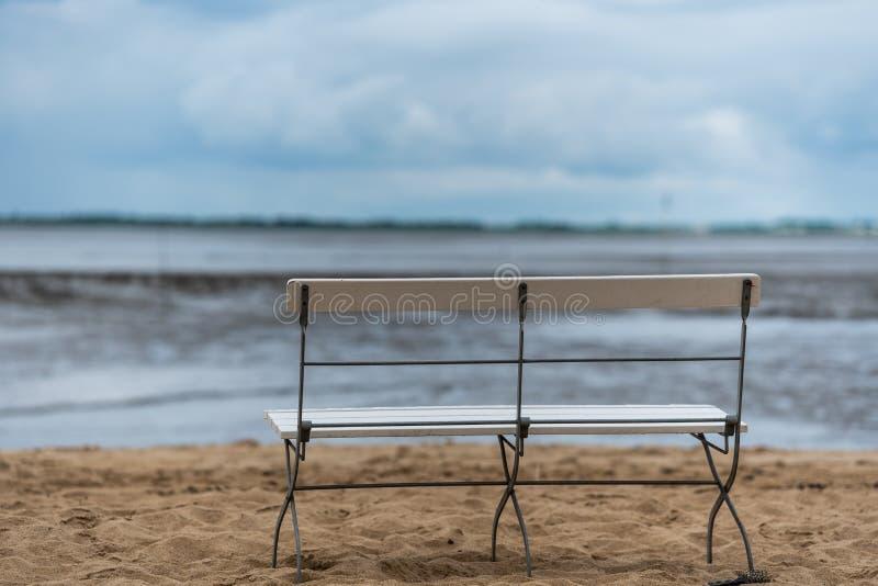 En ensam bank på en strand på ebbe arkivbilder
