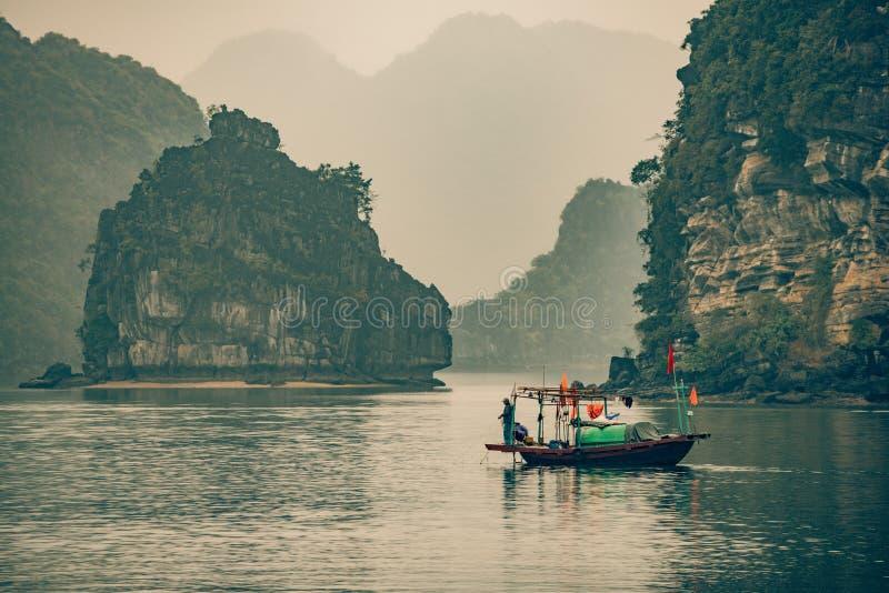 En ensam fiskare korsar vattnet i mummel skäller länge Vietnam royaltyfria foton