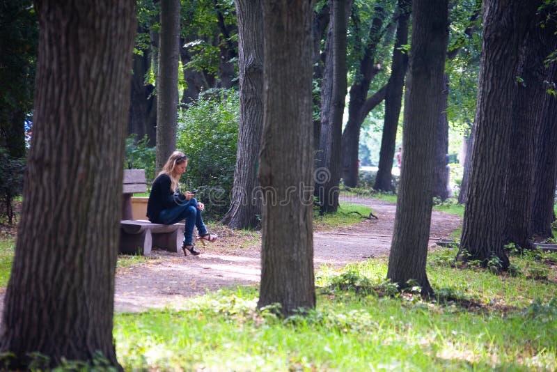 En ensam flicka sitter på en parkerabänk arkivbild