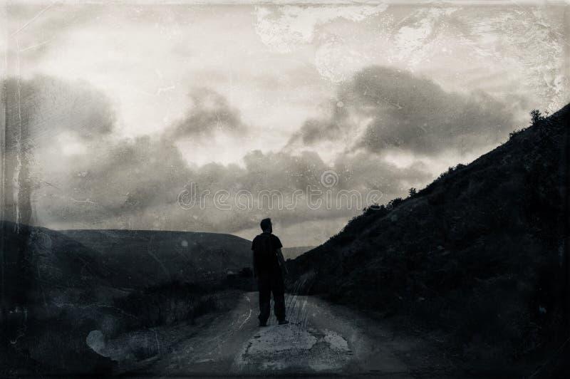 En ensam fotvandrare som upp ser en kulle på en mystisk lynnig bergväg Med ett mörker redigerar grunge, tappning royaltyfria foton