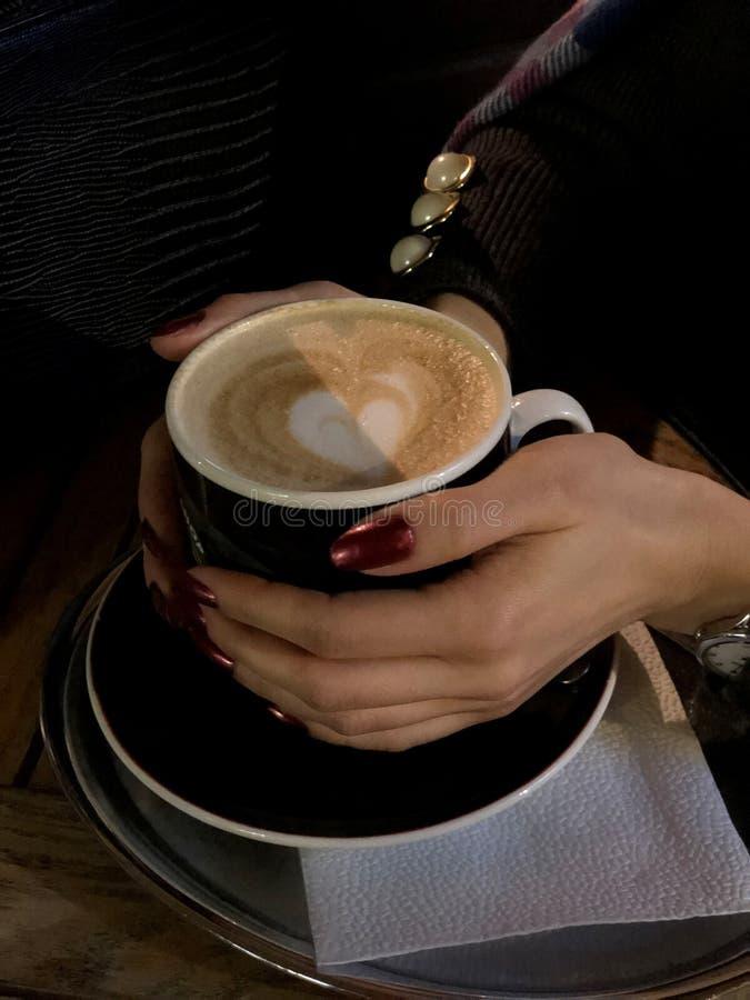 En ensam kvinna En kopp kaffe och en f?r?lskelse f?r varje person i deras h?nder royaltyfria bilder