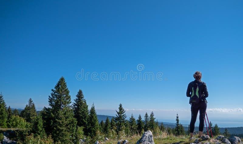 En ensam kvinnlig fotvandrare ser ut över en spektakulär sikt arkivbilder