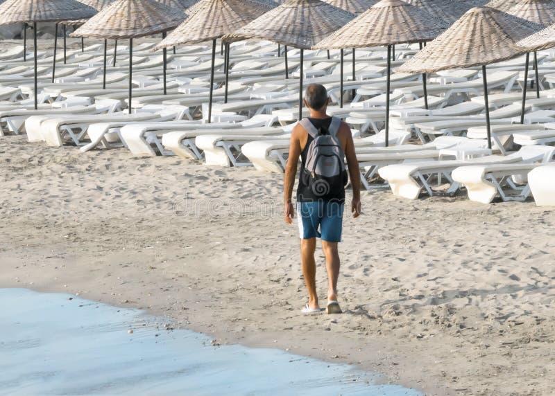 En ensam manlig handelsresande promenerar kusten med en ryggsäck på hans baksida Lokal strand på ön av Cypern arkivfoto