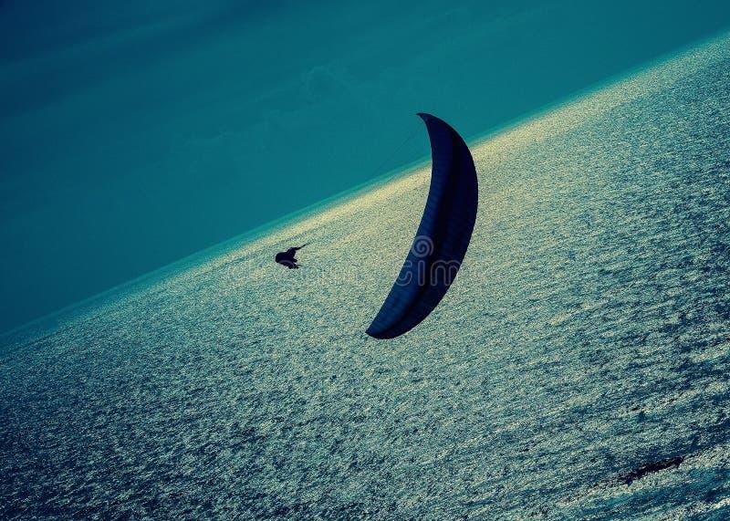 En ensam paraglider över ett silverhav med mörker fördunklar på aftonen royaltyfri foto