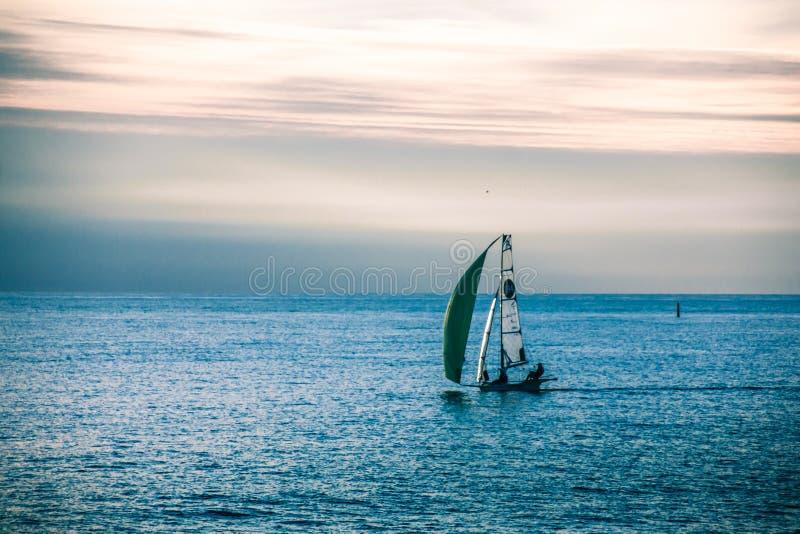 En ensam segelb?t i havet i slutet av dagen arkivfoton