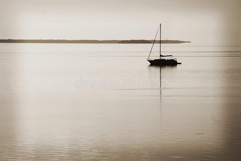 En ensam segelbåt i mitt av havet i de Florida tangenterna på skymning arkivbilder