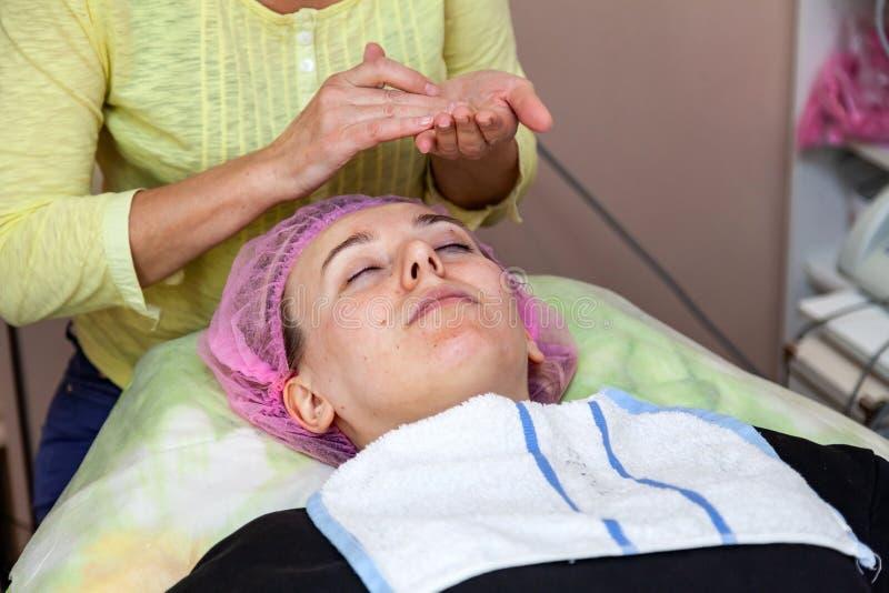 En erfaren cosmetologist applicerar en maskering av emulsion p? framsidan av en ung flicka som ligger p? soffan under ansikts- re royaltyfri foto