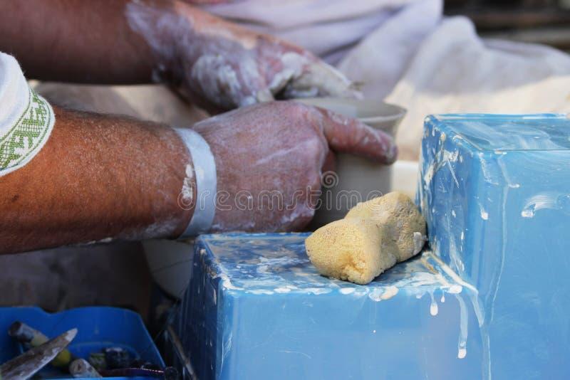 En erfaren ledar- keramiker undervisar en ung flicka att vända en kruka av lera på ett hjul för keramiker` s Reportageskytte royaltyfri bild