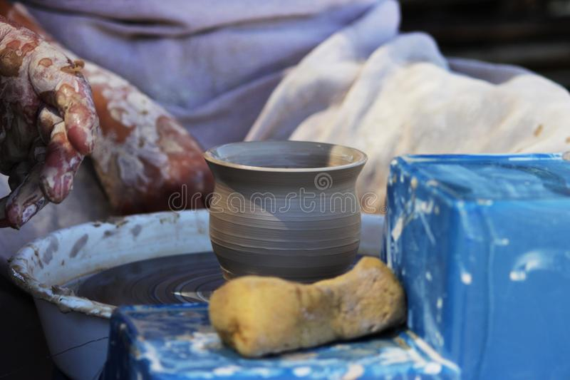 En erfaren ledar- keramiker undervisar en ung flicka att vända en kruka av lera på ett hjul för keramiker` s Reportageskytte arkivbilder