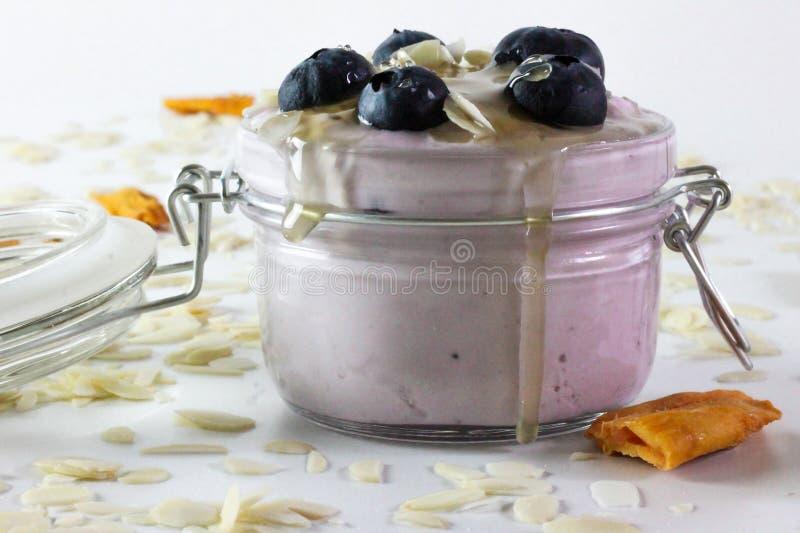 En esta foto podemos ver un yogur de arándano hecho a mano con los arándanos, las almendras y la miel Adornado alrededor con el m fotografía de archivo