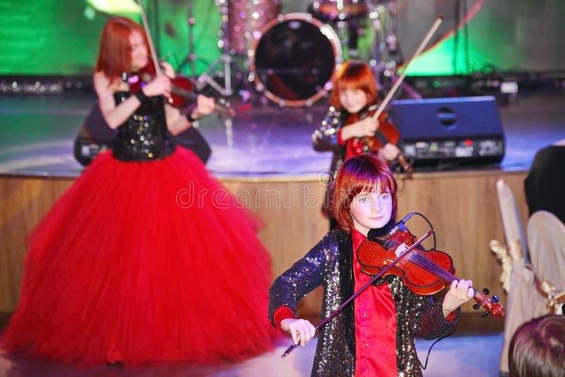 En etapa, los hijos pelirrojos expresivos de Maria Bessonova del violinista hermanan generaciones del trío dos del violín de músi imágenes de archivo libres de regalías