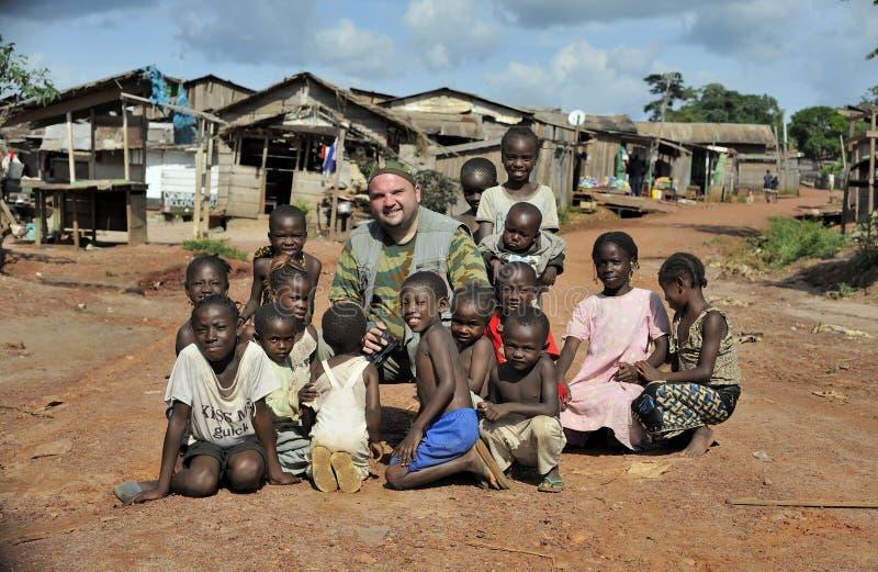En europeisk turist poserar med de lokala barnen på den lantliga vägen i en liten by i den centrala Afrika republiken royaltyfri foto