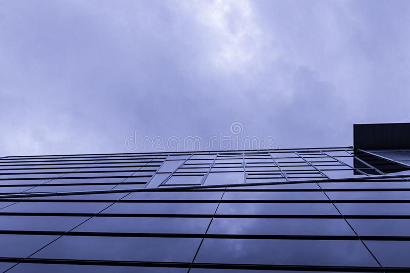 En exponeringsglasfasad nedanför en molnig himmel royaltyfria bilder