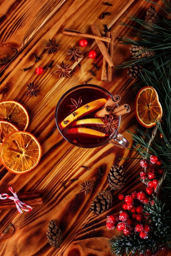 En exponeringsglaskopp av jul funderade vin eller gluhwein med kryddor och orange skivor p? lantlig tr?b?sta sikt f?r tabell arkivbild