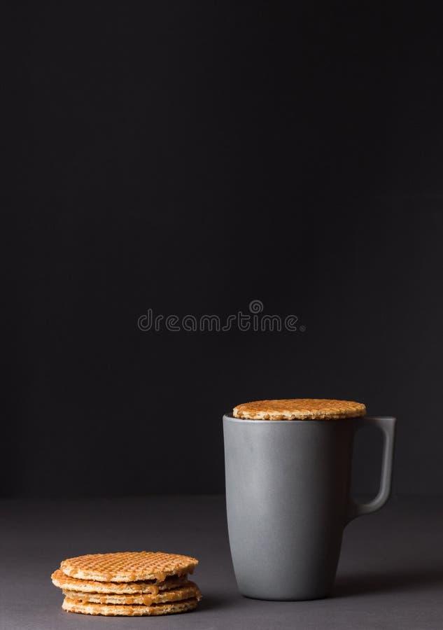 En exponeringsglaskopp av svart te med bunten av holländska dillandear på mörk grå bakgrund royaltyfri fotografi