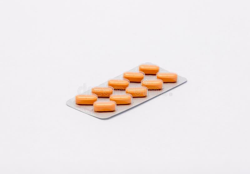 En färdig förseglad packe med orange rektangulära preventivpillerar ligger på en vit bakgrund fotografering för bildbyråer