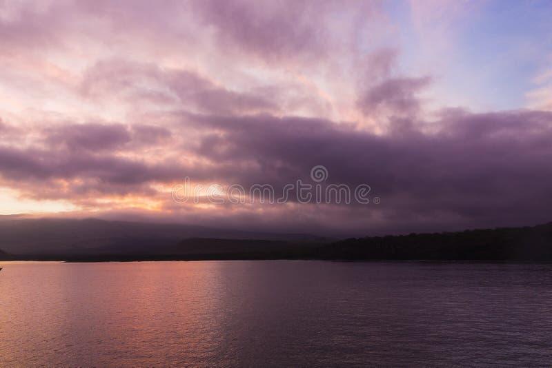 En färgglad soluppgång ovanför vattnet arkivfoto