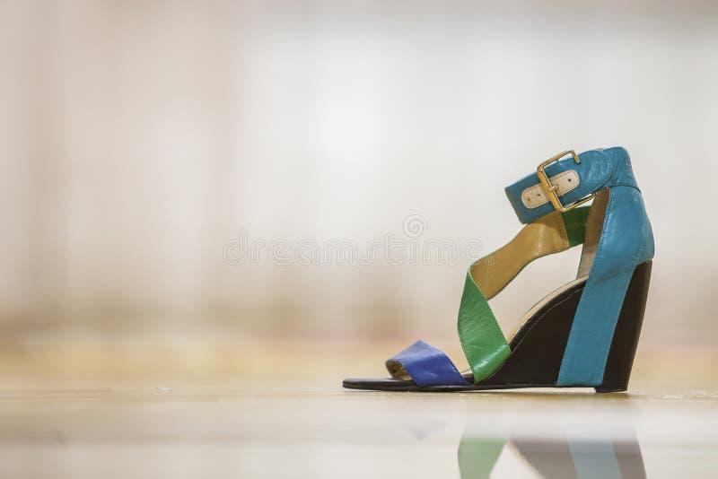 En färgrik ljus blå, grön och gul sandal för sko för läderrem kvinnlig på den höga svarta plattformen på ljust kopieringsutrymme arkivbilder