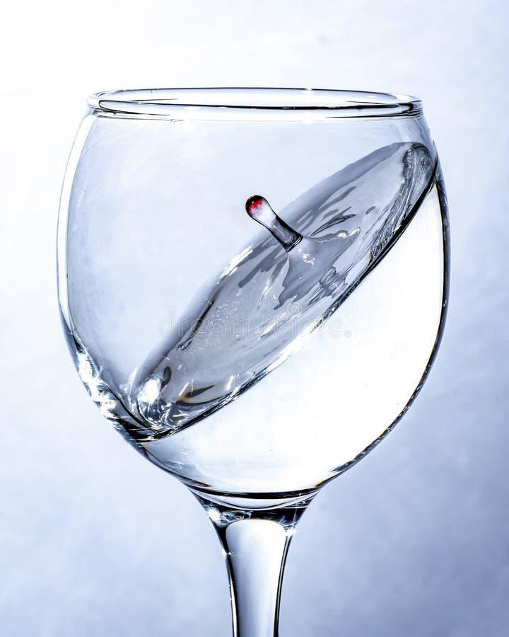 En färgstänk av vatten i ett exponeringsglas, en fallande droppe arkivbilder