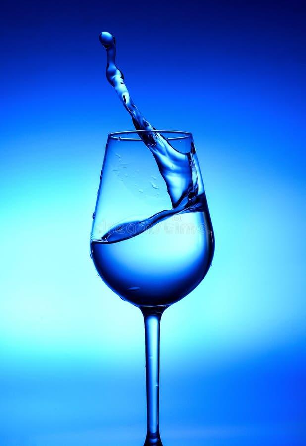 En färgstänk av vatten i ett exponeringsglas Vit-blått ljus i mitten och djupblått på kanterna arkivfoton