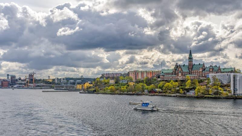 En färja för SL DJURGARDEN 8, kollektivtrafik av staden av Stockholm, passerande längs Danvikshem, storslagen gammal byggande hus royaltyfri foto