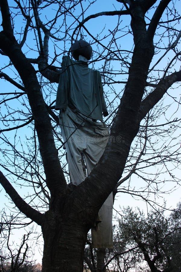 En fågelskrämma som hänger från ett träds hals royaltyfri foto
