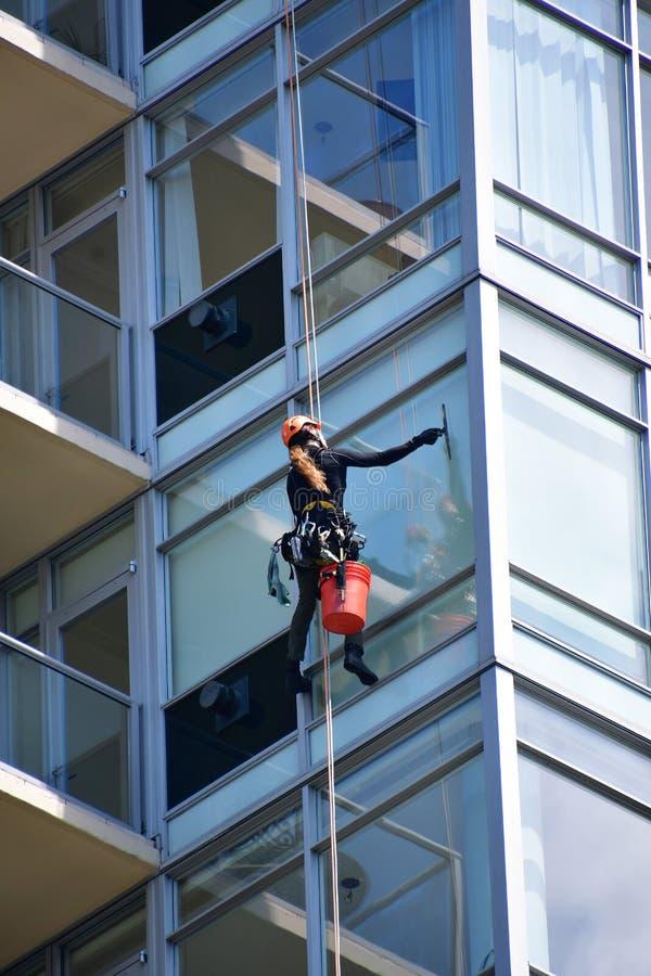 En fönsterpackning som gör ren fönstret av en hög löneförhöjningbyggnad fotografering för bildbyråer