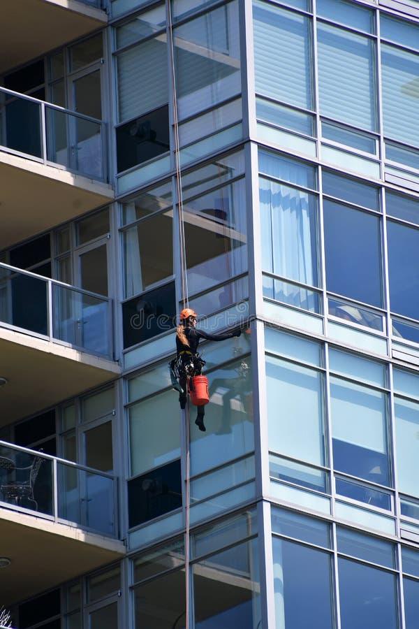 En fönsterpackning som gör ren fönstret av en hög löneförhöjningbyggnad royaltyfri fotografi