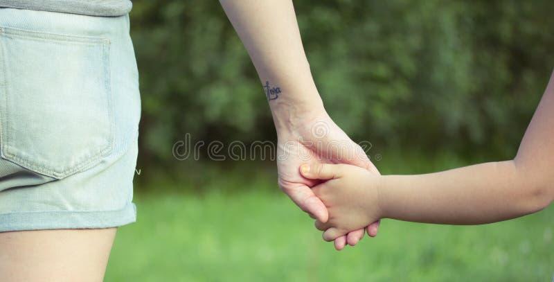 En förälder rymmer handen av ett småbarn royaltyfri fotografi