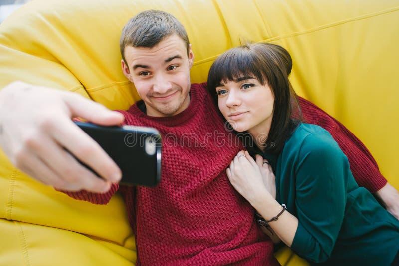 En förälskad hipstergyckel för unga par som gör selfie på din smartphone Stående av ungdomari rummet fotografering för bildbyråer