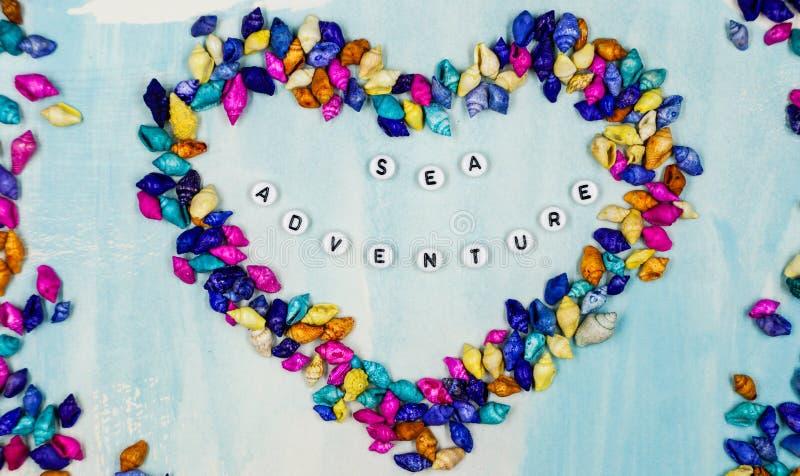 `en För affärsföretaget för uttrycks`-havet, har postats inom hjärtan av små färgrika skal på en blå bakgrund arkivbilder
