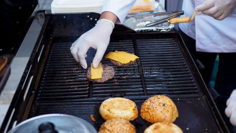En förberedelse av hamburgarenötkött som grillar på en varm gasugn royaltyfri bild