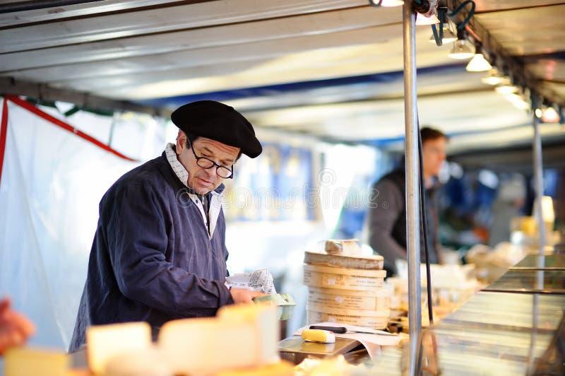 En försäljare som säljer ost på Paris bondejordbruksmarknad arkivbild