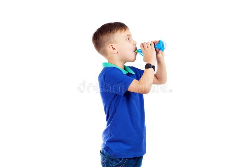 En förskole- pojke i en blå T-tröja spelar ett rör arkivfoto