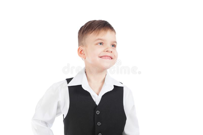 En förskole- pojke i en vit skjorta och svartwaistcoat ler vitt arkivfoto