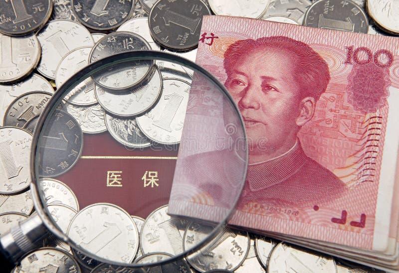 En förstoringsapparat med porslinyuanen på bakgrunden av bankboken för medicinsk försäkring arkivfoton