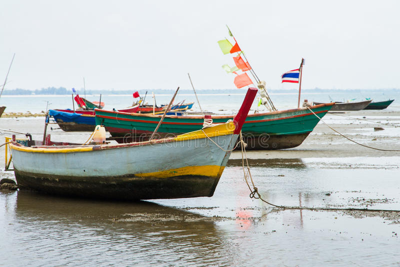 En förtöjd gammal fiskebåt satte på land på stranden på lågvatten arkivfoto