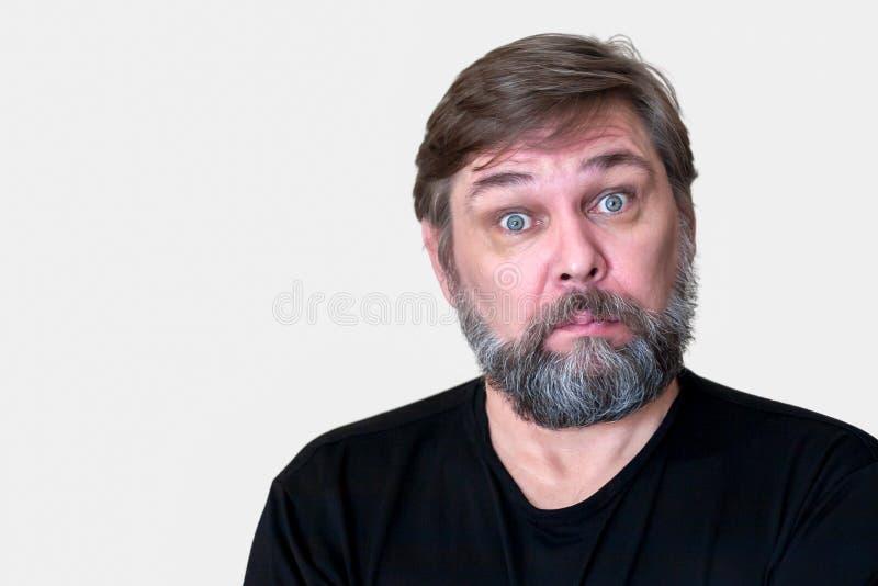En förvånad mitt åldrades mannen med ett skägg royaltyfria bilder