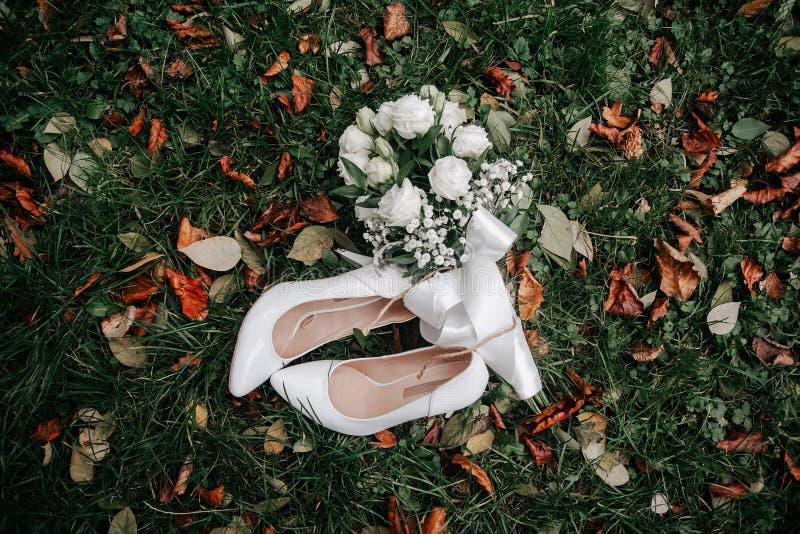 En f?rsiktig bukett f?r br?llop av vita och rosa rosor och h?g-heeled skor p? ett gr?nt gr?s i parkera den bl?a detaljblommagarte royaltyfri foto