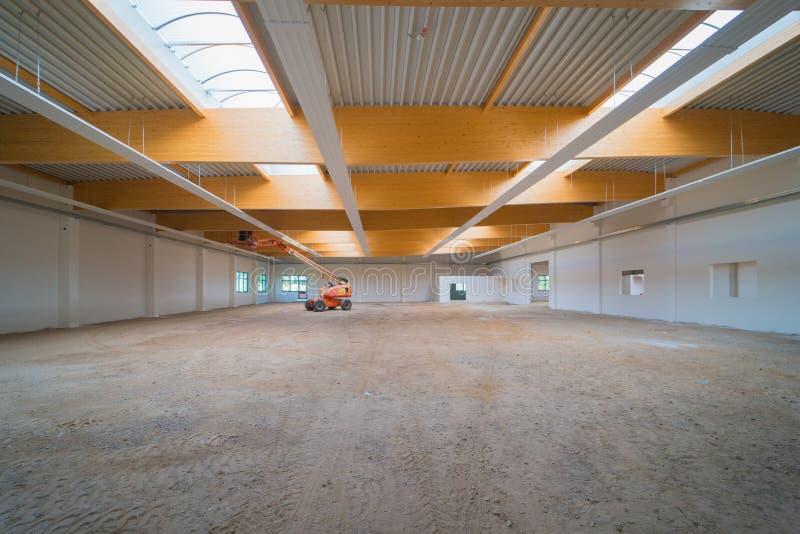 En fabrikskorridor är buret ut arbete med en lyftande plattform arkivfoto