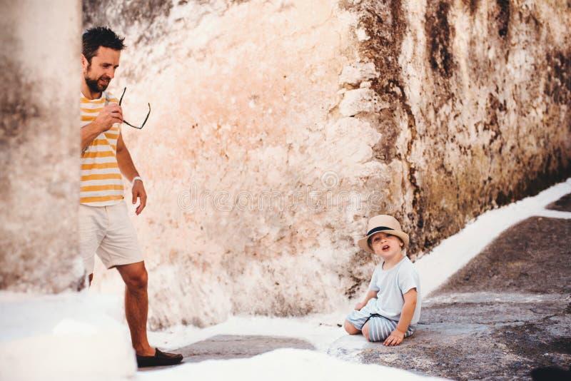 En fader med litet barnsonen i stad p? sommarferie royaltyfri fotografi