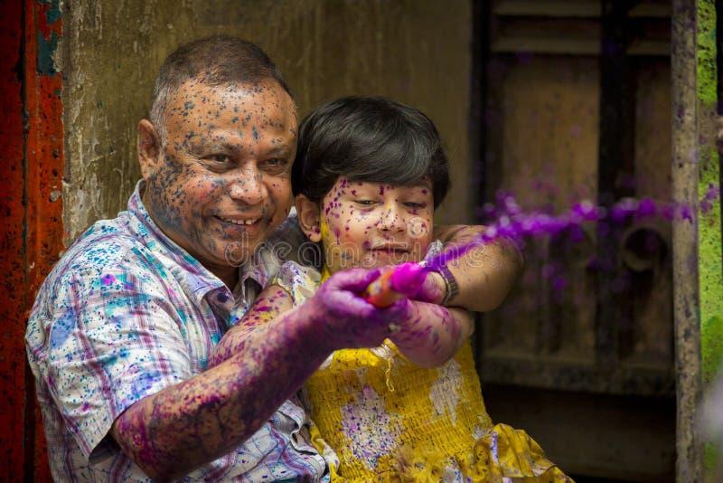 En fader och ett glat ögonblick för ungar av holien festivalen av färger i den Shakhari bazaren, Dhaka, Bangladesh royaltyfria bilder