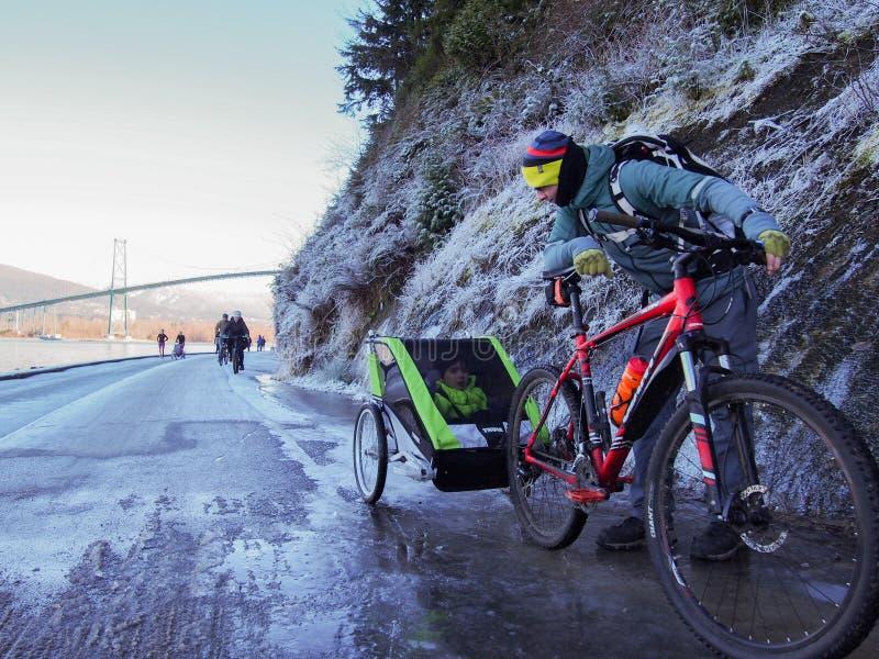 En fader och ungar i cykelsläp på skyddsmur mot havetcykeln skuggar i Stanl royaltyfri bild