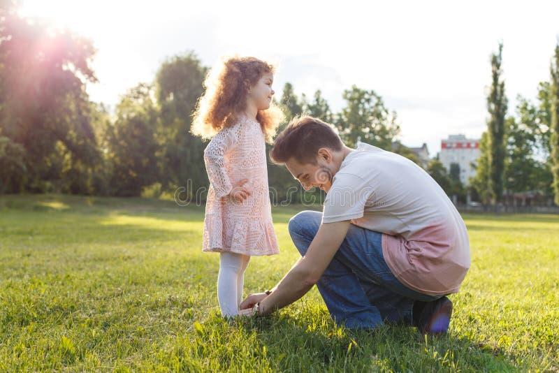 En fader som hjälper hans lilla dotter med hennes skor i parkera Gullig lockig ungeflicka i härlig klänning fotografering för bildbyråer
