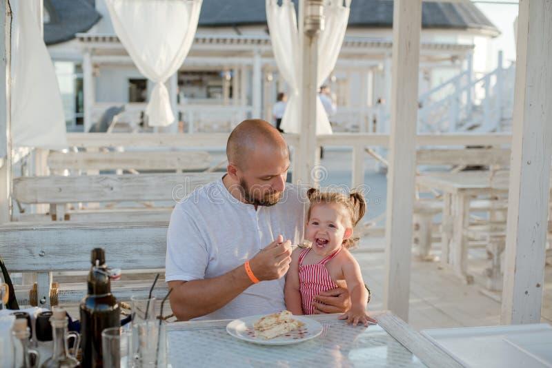 En fader som matar med en sked hans lilla dotter, medan sitta på en tabell i ett sommarkafé vid havet fotografering för bildbyråer
