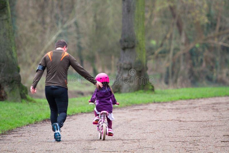 En fader undervisar hans dotter att rida en cykel arkivbild