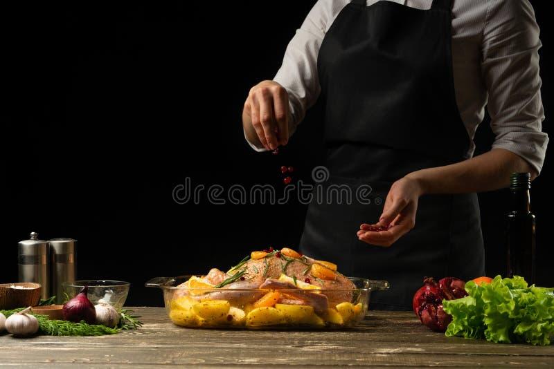 En faisant cuire le canard de chef arrosez avec des grains de grenade congelés, photo horizontale, fond noir images libres de droits