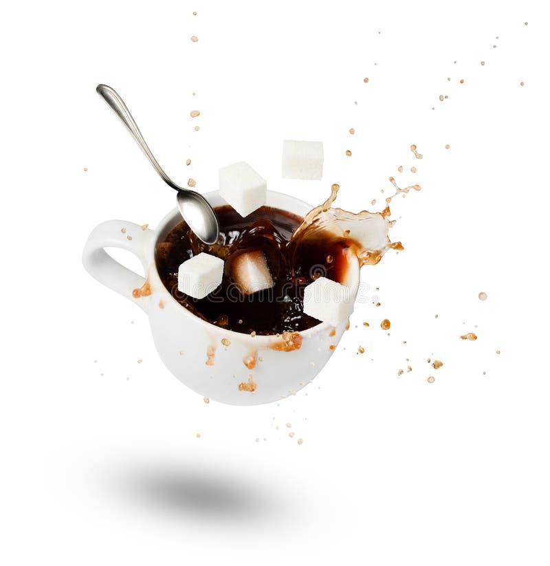 En fallande kopp kaffe, sockerkuber och en sked Bristningar och droppar rörelse skugga Vit isolerad bakgrund fotografering för bildbyråer