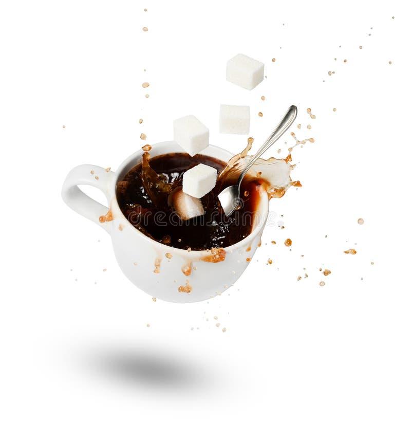 En fallande kopp kaffe, sockerkuber och en sked Bristningar och droppar rörelse skugga Vit isolerad bakgrund arkivfoton
