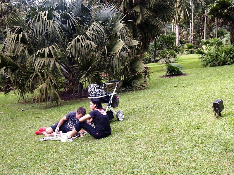 En familj av turisten sitter och vilar på gräset royaltyfria foton